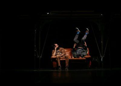 deux artistes de cirque contemporain sur un canapé faisant des acrobaties