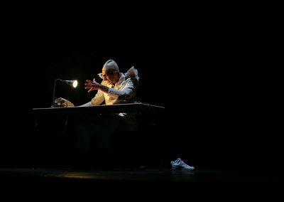 comédien jouant le rôle d'un ange et jouant avec une lumière de bureau